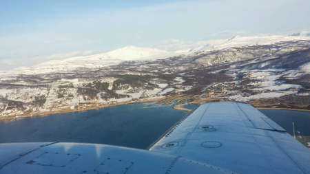 small plane: Majestic snowy mountain view in northern norway from small plane with tromsoe city in the background Stock Photo