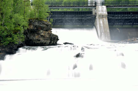 massive: massive white waterfall down rocks as water power plant opens concrete barrier