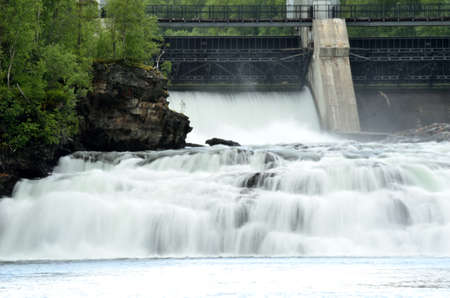 water power plant: massive white waterfall down rocks as water power plant opens concrete barrier