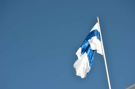 finland flag: finland flag on blue summer sky Stock Photo