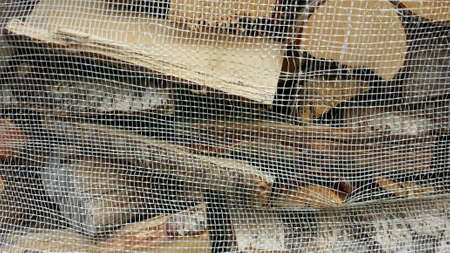 net: Firewood logs stacked in sack background Stock Photo