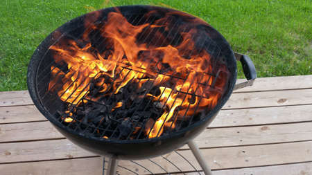 grill: Massive hot flames on barbeque grill on wooden patio in summer Stock Photo