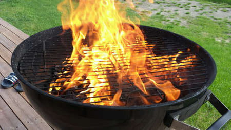 grill: Hot vivid flames on coal fueled barbeque grill in summer closeup Stock Photo