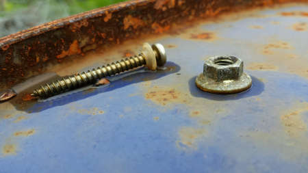 metal: Vibrant rusted screw and nut resting on top of blue metal barrel Stock Photo