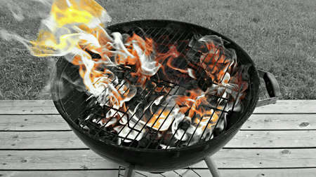 grill: Hot vibrant flames on barbeque grill on patio in summer
