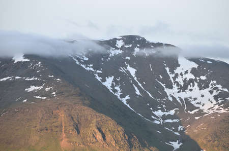 mighty: mighty mountain peak with clouds and snow patches in summer
