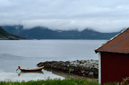 boat house: old red boat house with cloudy mountain range background and small docked boat