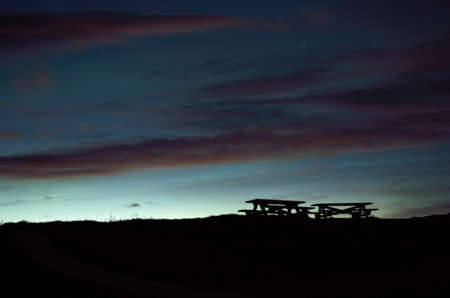 beautiful wooden park bench silouhettes with dawn sky background