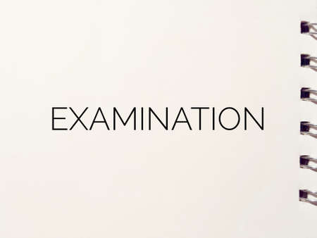examination written on white paper notepad Stock Photo