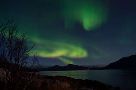 mighty aurora borealis dancing on night sky over mountain and fjord landscape in late autumn in the arctic circle Stock Photo