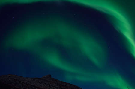northern light: massive swirly northern light dancing over mountain top in autumn night
