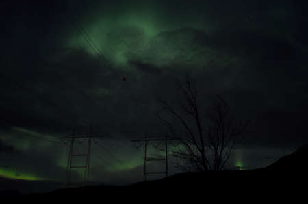 power grid: beautiful colorful aurora borealis dancing on night sky over massive power grid structure