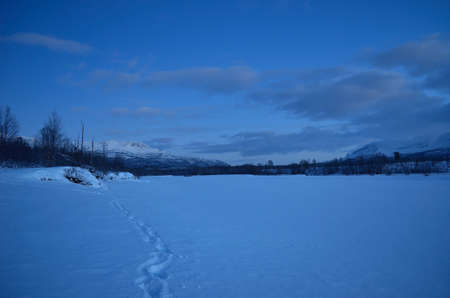 beautiful frozen river and mountain landscape in the high north winter Stock Photo