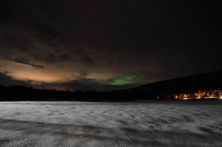 northern light: long white snowy field with green northern light in the background Stock Photo