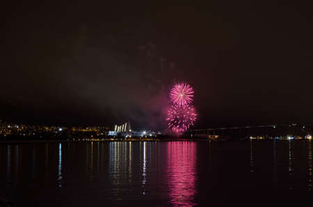 Beautiful firework on night sky in tromsoe city with bridge, cathedral and colorful reflection on the cold fjord water surface