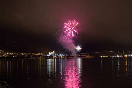 refelction: Beautiful firework on night sky in tromsoe city with bridge, cathedral and colorful reflection on the cold fjord water surface