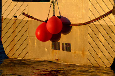buoys: fishing boat in harbor with red buoys hanging from the back with depth level marking