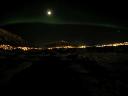 auroral: aurora borealis at night in tromsoe city with full moon