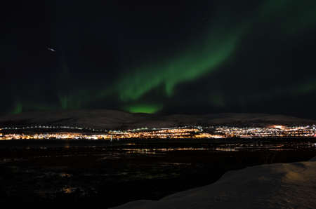 mighty northern light dancing over snowy mountain peak in northern norway on the whale island settlement