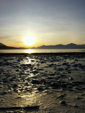 Golden sunset over frozen seashore and mountain range in the arctic circle