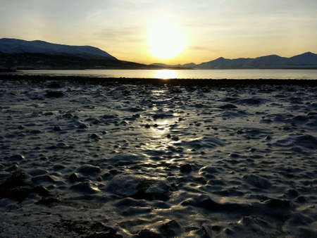 detail: Golden sunset over frozen seashore and mountain range in the arctic circle