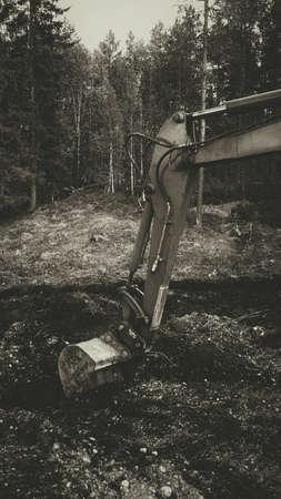 Excavator arm digging in mud brown frame