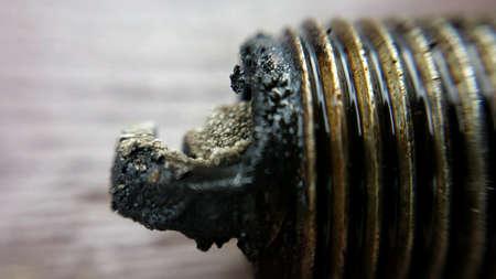 Old charred used car sparkplug macro photo