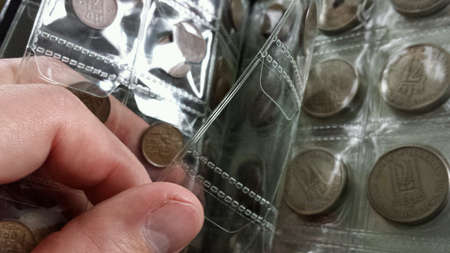 Turning pages in coin book with old norwegian coins Standard-Bild