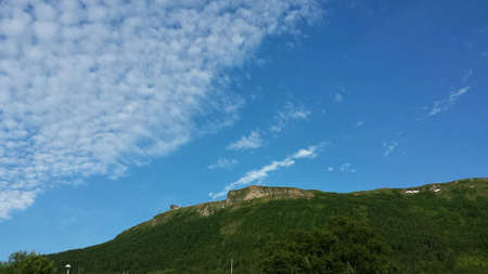 Deep blue sky with green hillside and mountain peak