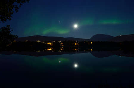 majestic aurora borealis, northern light over calm mirror lake at night with buildings in the background
