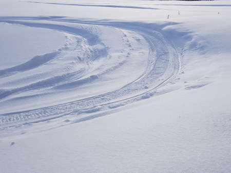 Snowmobile tracks on winter field
