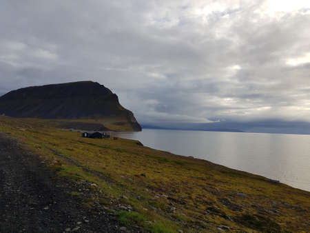 beautiful sea and mighty mountain landscape with small cabins in bear valley on svalbard Stock Photo