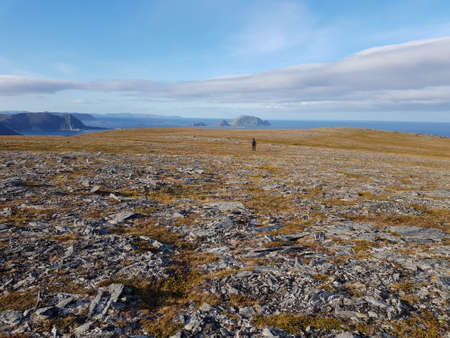 person on barren mountain with stunning sea view, northcape county1
