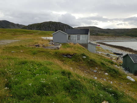 old weathered abandoned buildings on a rocky sea shore in northern norway