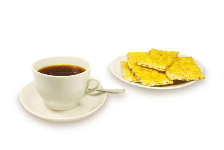 The white porcelain cup with black tea and carrot cookies on a white plate. On a white background photo