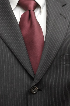 A pinstriped charcoal grey wool mens business suit with a silk tie and plain shirt.