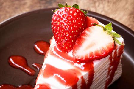 fresa: Crema de la torta y de la fresa con el grano de café en un plato negro. Foto de archivo