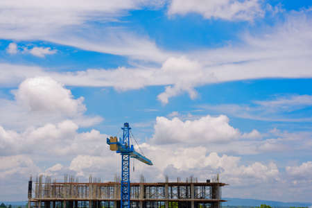 Crane on construction site and white cloud with blue sky background.
