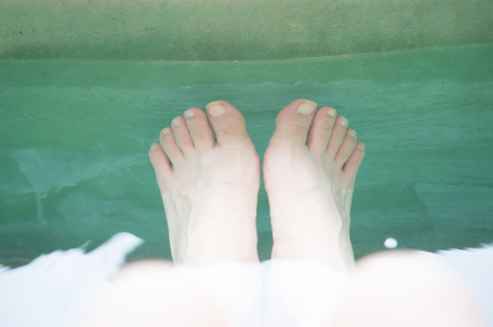 bared: Portrait of woman with bared feet relaxing on the water on her vacation.