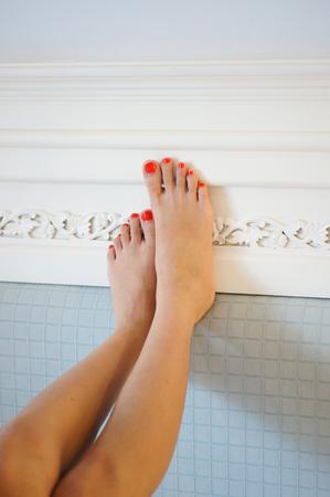 pies sexis: Sexy pies femeninos delgados con los clavos rojos de moda cuidadosamente pedicura en la cabecera