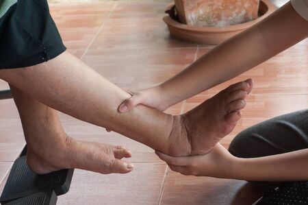 endearment: Young girls foot touches and holds an old womans wrinkled foot. Stock Photo