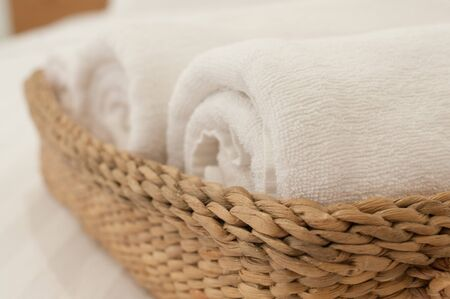 white towel: white towel on bed in white room Stock Photo
