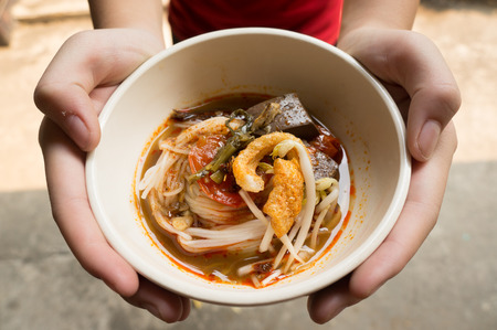 tangy: Rice noodles with spicy pork sauce (Nam ngiao) is a noodle soup or curry of the cuisine of the Tai Yai people. Nam ngiao has a characteristic spicy and tangy flavor. thai food.