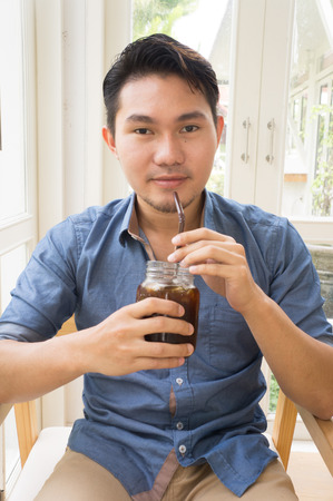 unrecognisable people: young man at wooden table drinking from cup