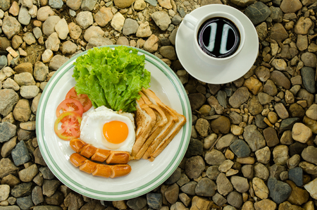 English breakfast with fried eggs, sausages,toasts, fresh salad and hot coffee or tea Stock Photo