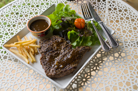 tbone: Waiter offering T-bone steak with french fries and hot sauce