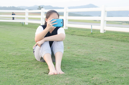 sitter: teenage girl in T-shirt  playing her smart mobile phone or iPad .