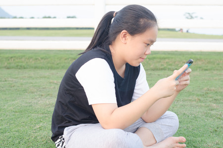 teenage girl in T-shirt  playing her smart mobile phone or iPad .