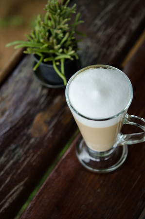 Coffee latte in a tall glass on the corner of wooden table Фото со стока