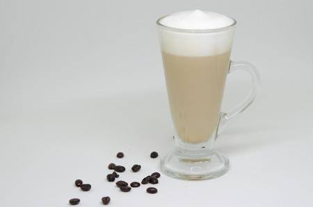 Coffee latte in a tall glass and coffee beans Фото со стока